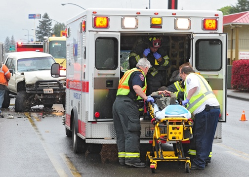 Brandon Swanson / bswanson@chronline.com First responders lift a man into an ambulance after he was involved in a car accident on Harrison Avenue in Centralia Wednesday.