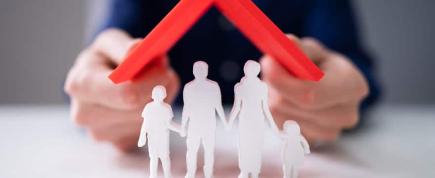 Businessman Protecting Family Figures With Red Roof